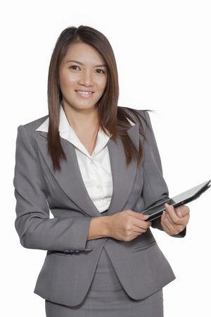 smilling: Portrait young pretty businesswomen in office attractive standing using a tablet smilling and happiness Stock Photo