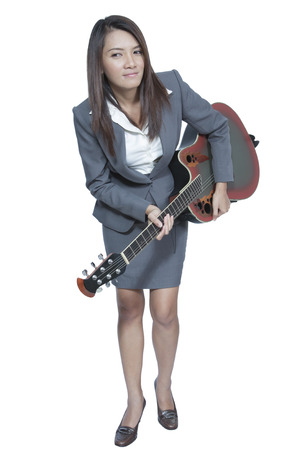 Young Asian business woman in suit playing guitar isolated on white background photo