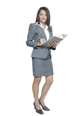 Donna d'affari attraente giovane ragazza in piedi in ufficio godere con un libro penna diario di scrittura nota sorridente positivo su sfondo bianco Archivio Fotografico - 24826838