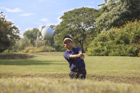 Giovane giocatore di golf maschile in camicia blu e pantaloni grigi cippatura pallina da golf da un separatore di sabbia con cuneo di sabbia e sabbia catturati in movimento Archivio Fotografico - 28824843
