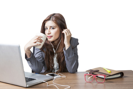 Business woman attractive beautiful   sitting at office desk and enjoy with listening music and drinking coffee relaxation smile photo