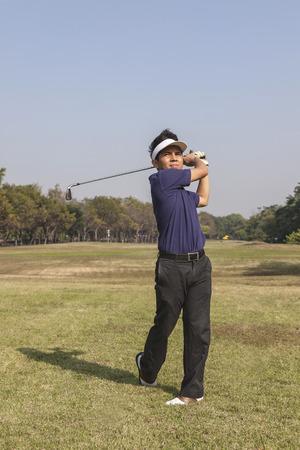 pga: Golfer swinging his club in green grass on a sunny summer day Stock Photo