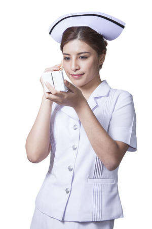 Young woman asian nurse attractive beauty brunette holding face powder for make up in white background Stock Photo - 29205840