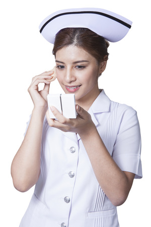 ady: Young woman asian nurse attractive beauty brunette holding face powder for make up in white background