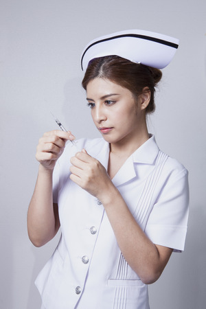 Young woman asian nurse attractive beauty brunette focus holding hypodermic syringe in white background photo