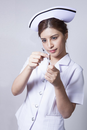 ady: Young woman asian nurse attractive beauty brunette focus at holding hypodermic syringe in Grey background