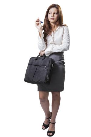 full length brunette businesswoman holding handbag and bored isolated on white background photo