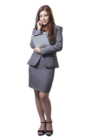 Young businesswoman standing holding digital tablet isolated on white background  Beautiful mixed race Asian with finger on touch screen display photo