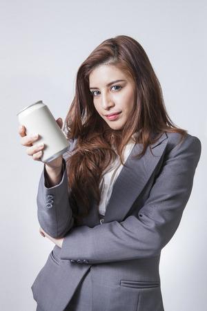 Bruna giovane di affari che presenta una lattina di bibita isolato su sfondo bianco Archivio Fotografico - 29565345