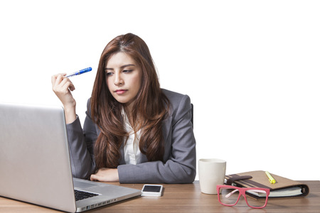 Businesswoman boredom in the workplace with a laptop, cup, coffee, glasses, a pen isolated on white background Stock Photo