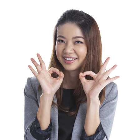 Perfect - business xwoman showing OK hand sign smiling happy  Young pretty Asian   Caucasian businesswoman isolated on white background  photo