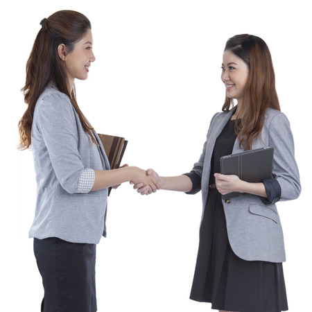 Two beauty businesswomen handshaking smiling on white background photo