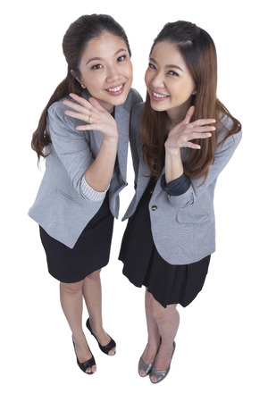 Two beautiful businesswomen having a happy post take a photo isolated on white background photo