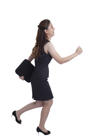 Young Pretty Businesswoman running in suit in full body isolated on white background. Business concept image with young mixed race Caucasian  Chinese Asian businesswoman. photo