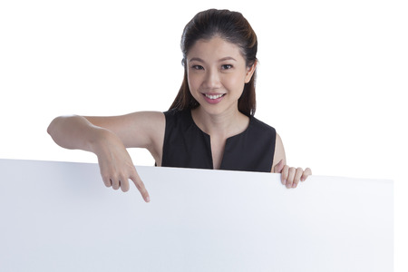Woman showing and pointing at blank billboard sign banner, Young smiling Chinese Asian  Caucasian female model. Isolated on white background. photo