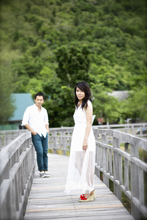 The groom and the bride standing on the wooden bridge by the lake and looking at each other. photo