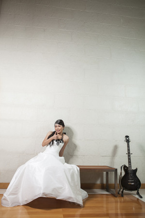beauty bride sitting on wooden bench white . photo