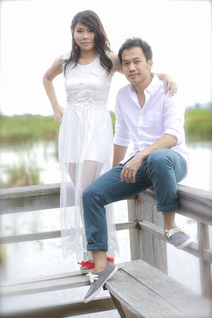 prewedding: groom and bride standing on the wooden bridge in beauty lake .