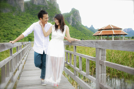 prewedding: The groom and the bride standing on the wooden bridge by the lake and looking at each other. Stock Photo