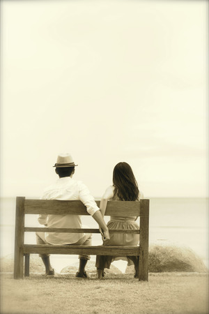 A bride and groom sitting wooden bench on the beach Stock Photo