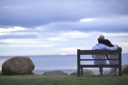 A bride and groom sitting wooden bench on the beach photo