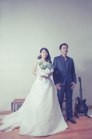 Portrait of Caucasian groom and Asian bride photo