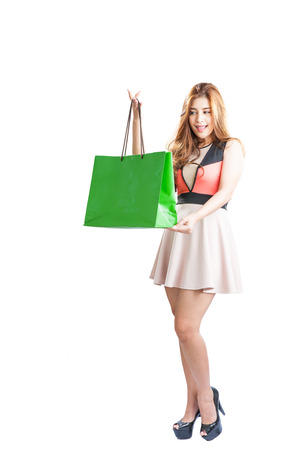 Shopping woman happy looking at empty copy space. Isolated on white background. Beautiful Asian Caucasian female shopper photo