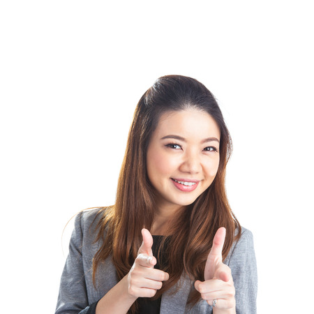 Smiling xwoman in white pointing at your product while looking at the camera. Isolated on white background. Beautiful mixed asian photo