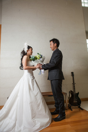 Bride and groom with bouquet of flowers in the wedding with guitar on white background. photo