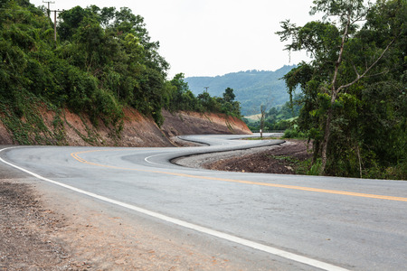 s curve: A rural mountain road with a winding S curve. The road fades into darker tones as it moves away from the viewer.in Thailand.