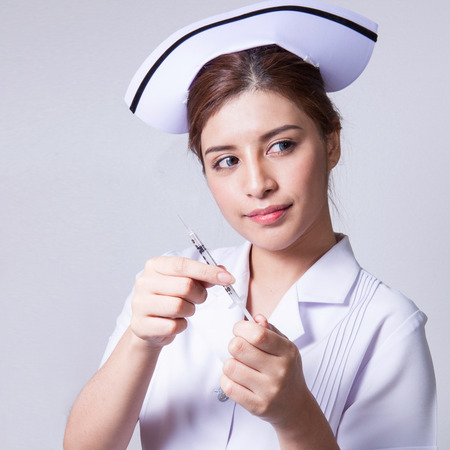 ady: Young woman asian nurse attractive beauty brunette focus holding hypodermic syringe in white background