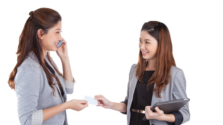 Two pretty businesswomen exchanging business cards on white back ground Stock Photo