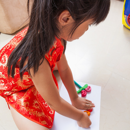 playful behaviour: Little girl creating toys from playdough Stock Photo