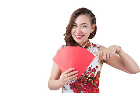 red envelope: Happy chinese new year. smiling young Asian woman holding red envelope.  beauty chinese woman dress traditional cheongsam at New Year, studio shot isolated on white background. Stock Photo