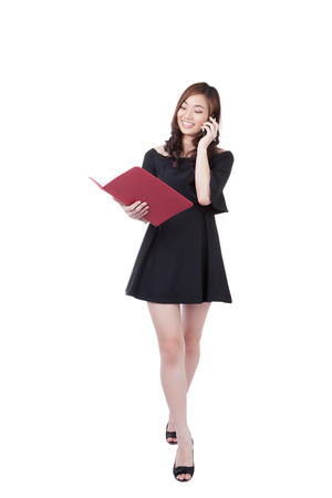chinese woman: Businesswoman walking talking on mobile phone and hold daily. Young stylish business woman smiling isolated on white in full body. Mixed-race chinese asian  white caucasian brunette female model.