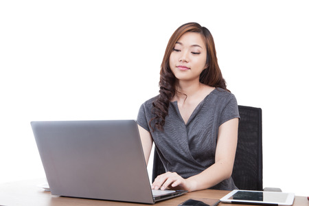 Businesswoman using laptop computer at office. Mixed race chinese / caucasian model isolated on seamless white background. Stock Photo