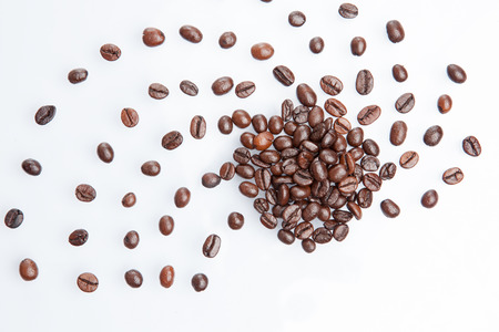 processed grains: Heap of coffee beans isolated on white background.
