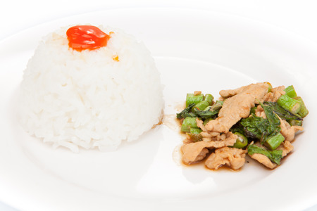 Thai food, kapao moo,  pork with basil, minced pork fried with chilli pepper and sweet basil. Close-up with shallow depth of field. on white plate set photo