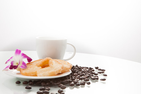 continental breakfast: Continental breakfast with assortment of pastries, coffees and flower Orchid in studio shot on coffee beans and white background. Stock Photo