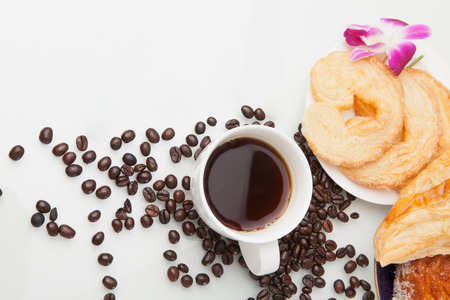 coffees: Continental breakfast with assortment of pastries, coffees and flower Orchid in studio shot on coffee beans and white background. Stock Photo