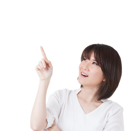 Pointing and looking to the side. Casual young businesswoman in white shirt looking, pointing and smiling at copy space. Beautiful young mixed race Chinese  caucasian xwoman isolated on white.