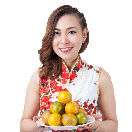 chipao: Happy chinese new year. smiling beauty Asian woman showing oranges for worship and lucky. get rich and happy, Isolated on white background. Stock Photo