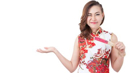 personas saludandose: Feliz año nuevo chino. sonriente joven mujer asiática sosteniendo sobre rojo.  Belleza chino cheongsam tradicional vestido de mujer en Año Nuevo, foto de estudio aislado sobre fondo blanco. Foto de archivo