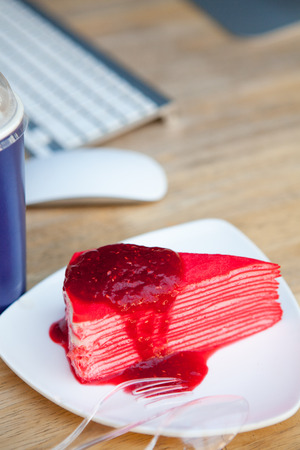 table wood: Crepe cake with strawberry sauce in white plate and coffee on wood table Stockfoto
