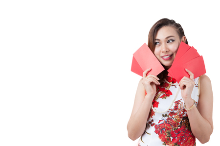 chipao: Happy chinese new year. smiling young Asian woman holding red envelope.  beauty chinese woman dress traditional cheongsam at New Year, studio shot isolated on white background. Stock Photo
