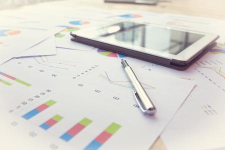 Ambiente di lavoro moderno di affari con l'applicazione dei dati del mercato azionario, penna e una tavoletta digitale, su un tavolo di legno. Archivio Fotografico - 47354346