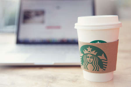 starbucks: A tall Starbucks coffee in front of working on a laptop computer. Stock Photo