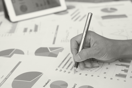 bw: B&W  Close-up of businessmen working with financial document and tablet.