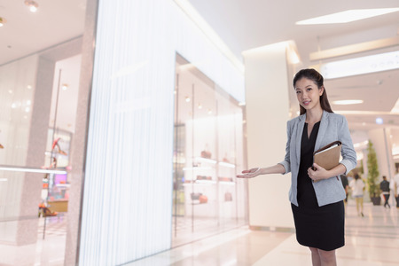 sopping: Young businesswoman present to offer products and handbag and shoe store Which are on sale at shopping mall.