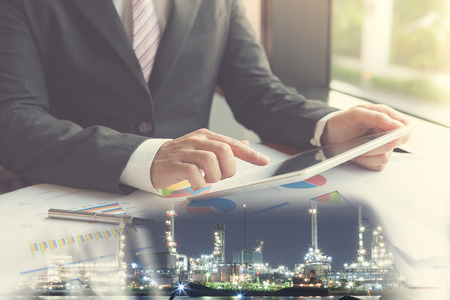 Double exposure businessman using the tablet in office with refinery and financial graph on blurred oil refinery background, Business Trading concept.